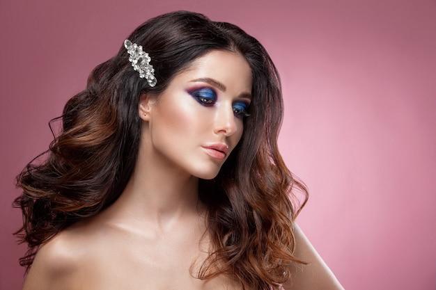 Rosto de mulher de beleza com bela cor de maquiagem. cabelo escuro, cabelo levantado, joias no pescoço, pele limpa, rosto bonito. retrato filmado em estúdio em um fundo rosa.