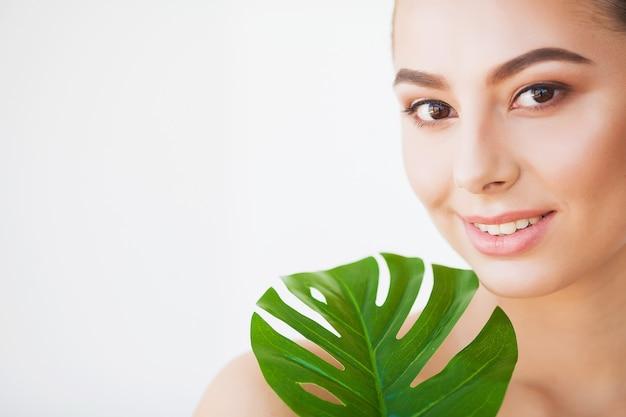 Rosto de mulher de beleza com pele saudável e planta verde