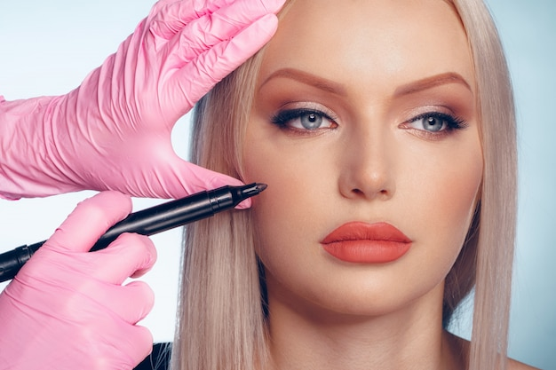 Rosto de mulher e mãos de médico com lápis. cirurgia plástica