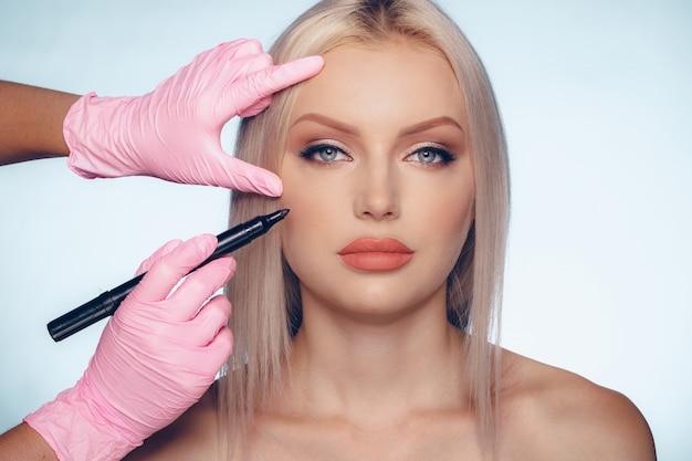 Rosto de mulher e mãos de médico com lápis, conceito de cirurgia plástica