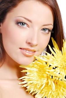 Rosto de mulher jovem bonita em close-up com a camomila amarela