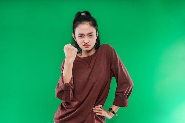 Rosto de mulher jovem com uma expressão de raiva enquanto fecha um punho e uma mão na cintura contra um fundo verde