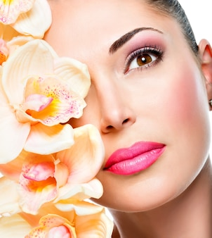 Rosto de mulher jovem e bonita com pele saudável e flores brancas - isolado no branco