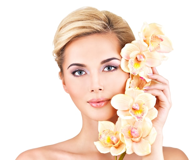 Rosto de mulher jovem e bonita com pele saudável e flores cor de rosa no corpo - isolado no branco