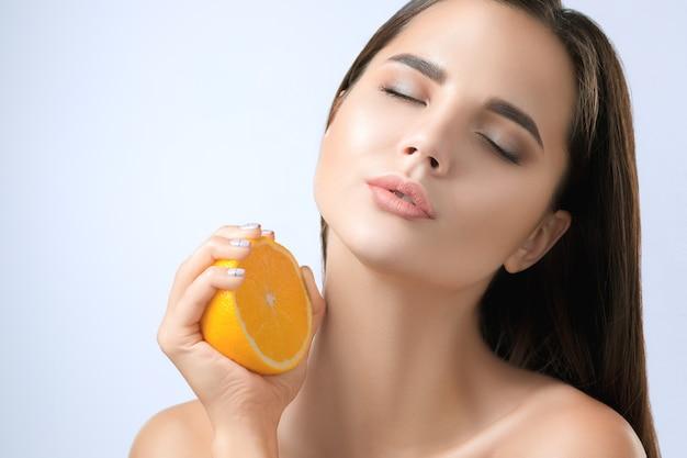 Rosto de mulher linda com laranja deliciosa