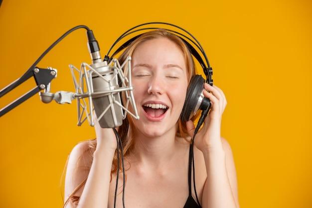 Rosto de mulher ruiva linda cantando com uma boca aberta do microfone prata condensador realizando pose de música sobre espaço de cópia de parede amarela para o seu texto. locutor de rádio fm.