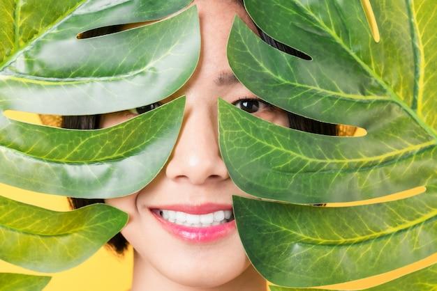 Rosto de mulher sob folhas verdes