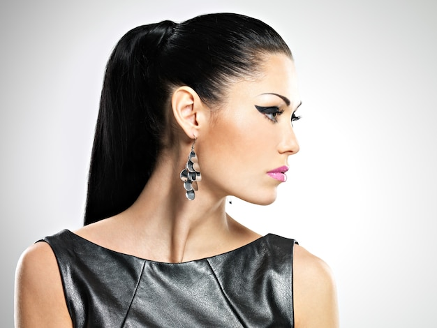 Rosto de perfil da bela mulher sexy com maquiagem de moda glamour dos olhos e penteado de brilho. retrato da menina adulta caucasiana em estúdio
