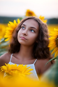 Rosto de retrato de menina adolescente no campo de girassóis.