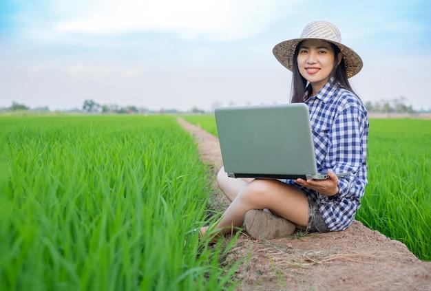 Rosto de sorriso de mulher jovem asiático agricultor sentado e usando o laptop na fazenda de arroz verde