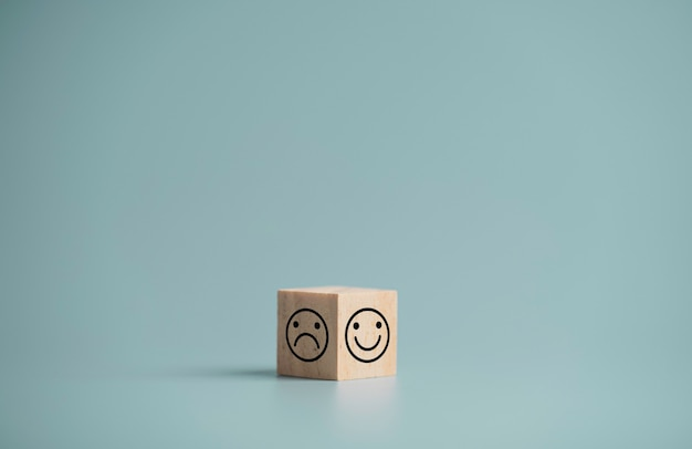 Rosto de sorriso e rosto de tristeza imprimem tela de dois lados de um bloco de cubos de madeira sobre fundo azul