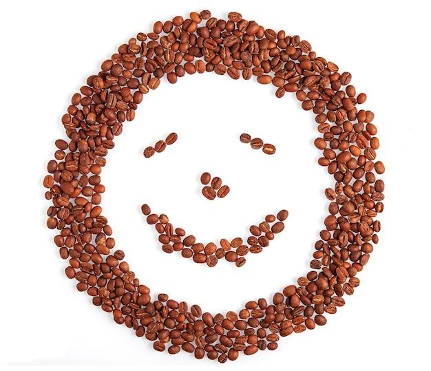 Rosto de sorriso feito de sorrisos de grãos de café e prazer isolado no fundo branco