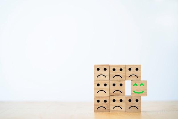Rosto de sorriso que imprime tela em bloco de cubo de madeira se move de triste emoção