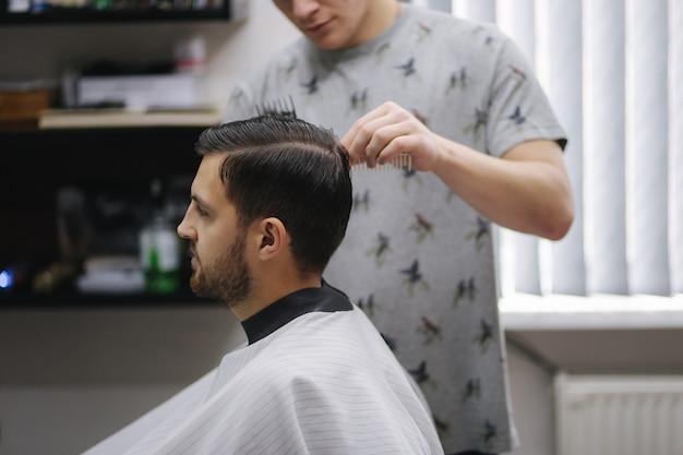 Rosto de um cara cortando o cabelo em um salão de cabeleireiro. o cabeleireiro também usa máscara. o cabelo tem como o afro