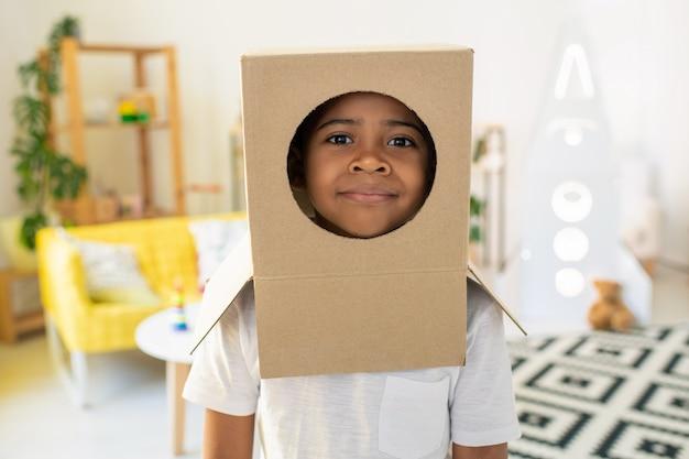 Rosto de um garotinho fofo de etnia africana através de um buraco em uma caixa de papelão na cabeça