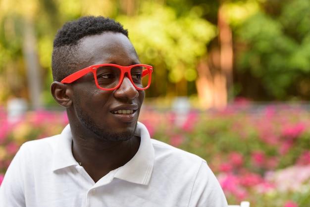 Rosto de um jovem africano feliz com óculos pensando ao ar livre no parque