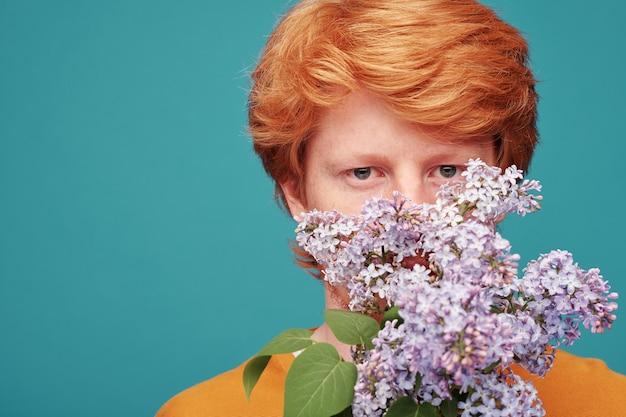 Rosto de um jovem com cabelo vermelho olhando para você por trás de um ramo ou um perfume lilás florescendo contra uma parede azul
