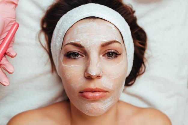 Rosto de uma garota com uma máscara de creme close-up
