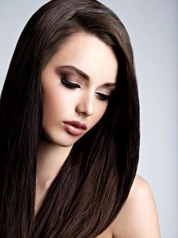 Rosto de uma jovem bonita com maquiagem marrom e cabelo liso