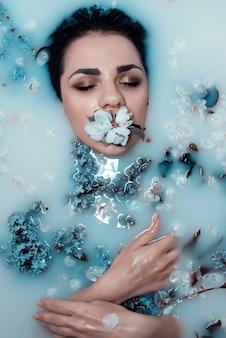 Rosto de uma jovem garota com uma flor na boca e um buquê de lilases relaxando e curtindo no banho com leite azul