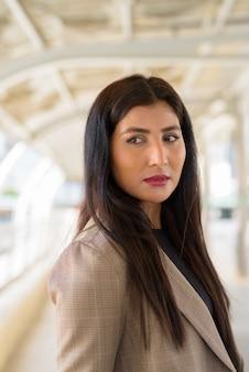 Rosto de uma jovem linda empresária indiana pensando em uma passarela na cidade