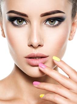 Rosto de uma jovem mulher bonita com unhas multicoloridas