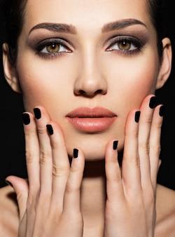 Rosto de uma linda garota com maquiagem fashion e unhas pretas posando no estúdio sobre um fundo escuro