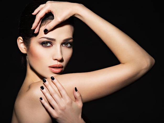 Rosto de uma linda garota com maquiagem fashion e unhas pretas posando sobre uma parede escura