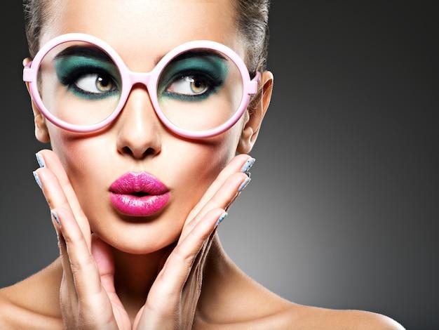 Rosto de uma linda garota expressiva com maquiagem fashion em óculos rosa