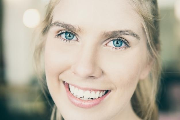 Rosto de uma linda jovem loira feliz com olhos azuis e dentes brancos