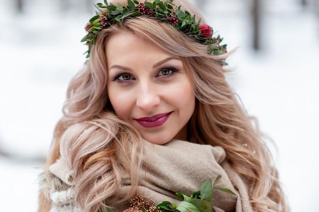 Rosto de uma menina sorridente de aparência eslava com uma coroa de flores silvestres. linda noiva segura um buquê em plano de inverno. fechar-se