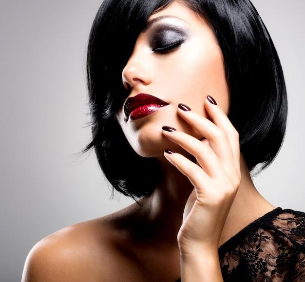 Rosto de uma mulher com lindas unhas escuras e lábios vermelhos sensuais. modelo com cabelos pretos arrepiados