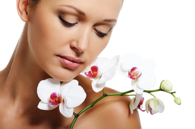 Rosto de uma mulher muito bonita com uma orquídea branca no ombro