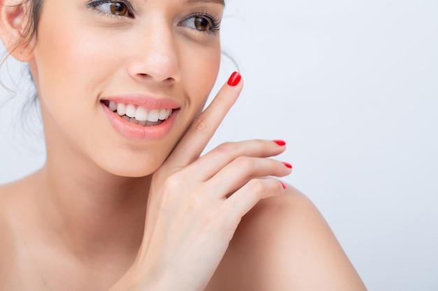 Rosto em forma de v de beleza de modelo jovem asiática com maquiagem natural tocar seu rosto em um fundo branco com espaço de cópia