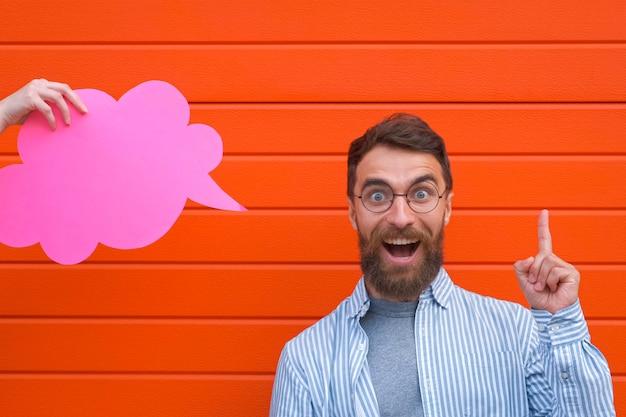 Rosto emocional de homem segurando um balão de fala olhando para a câmera