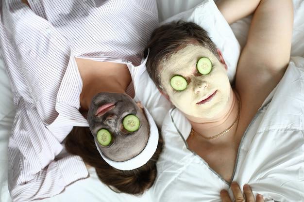 Rosto fechar máscara cosmética e fatia de pepino nos olhos.