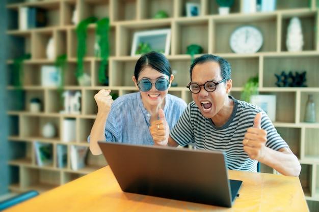 Rosto feliz da família asiática olhando para um laptop