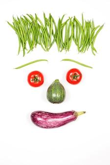 Rosto feliz vertical com vegetais no fundo branco