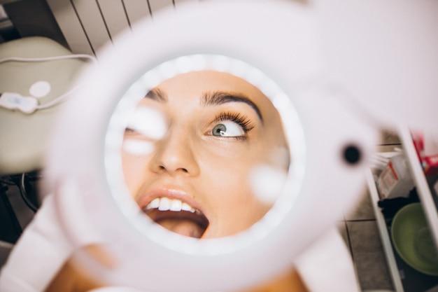 Rosto feminino através da lente de aumento em um salão de beleza