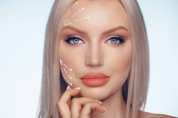Rosto feminino bonito, branco, marcado com setas nas principais linhas de lifting facial, close-up