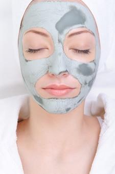Rosto feminino cândido e jovem com máscara cosmética de argila