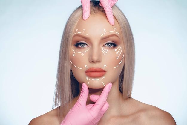 Rosto feminino caucasiano bonito marcado com setas nas principais linhas de levantamento facial