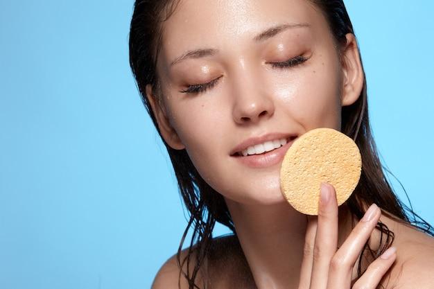 Rosto feminino com gotas de água e cabelo molhado limpando o rosto com esponja com os olhos fechados