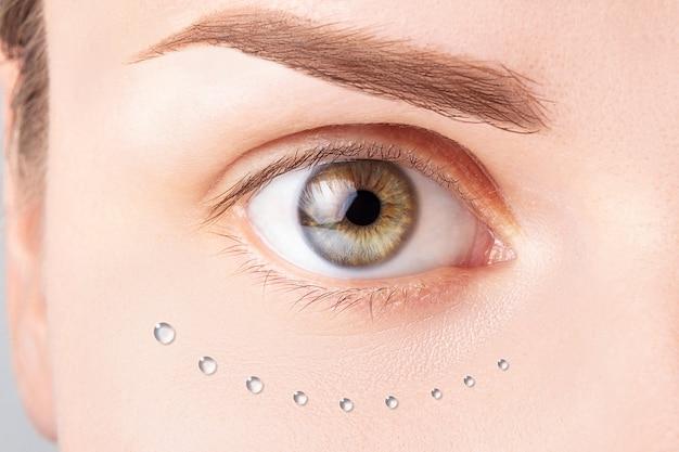 Rosto feminino com gotas de água na pele. revitalização biológica, conceito de hidratação da pele