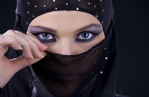 Rosto feminino de ninja no escuro