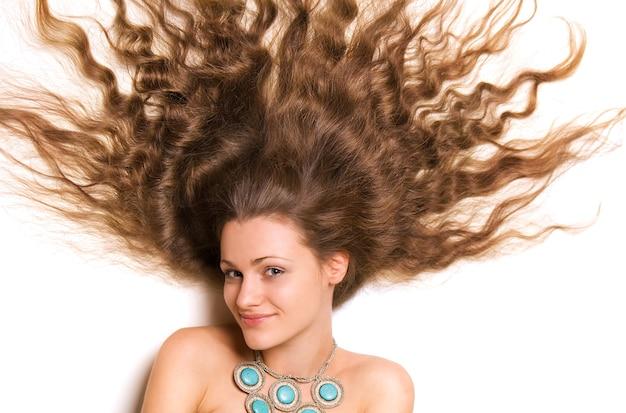 Rosto feminino jovem bonito, com longos cabelos loiros encaracolados