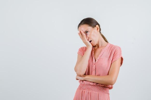 Rosto feminino jovem inclinado na palma da mão levantada em vestido listrado e parecendo irritado, vista frontal.