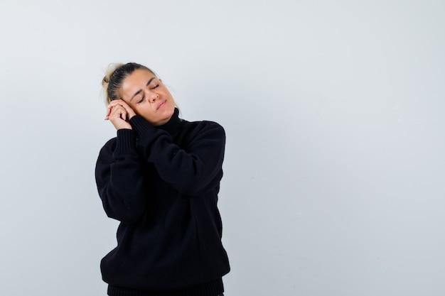 Rosto feminino jovem travesseiro nas mãos entrelaçadas na camisola de gola alta preta e parecendo com sono. vista frontal.