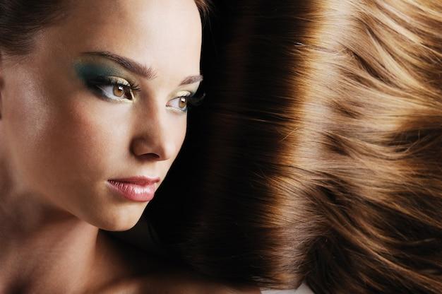 Rosto feminino lindo em close-up com cabelos longos exuberantes como um espaço
