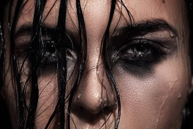 Rosto feminino molhado com uma maquiagem borrada